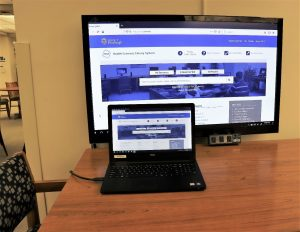 Large screen displaying a webpage from a connected laptop