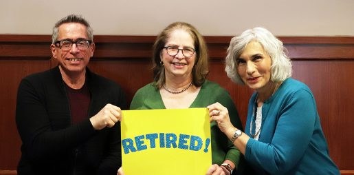 Smiling librarians hold a sign with the word Retired!