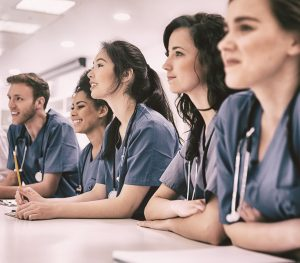 Medical students listening sitting at desk