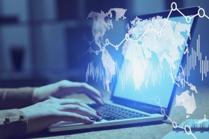 Woman hands typing on laptop in blurred office with double exposure of world map and graphs.