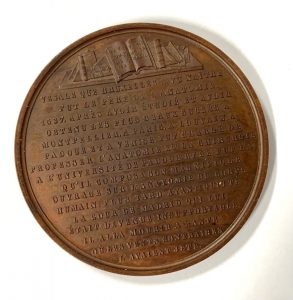 Books and French transcription on a medal